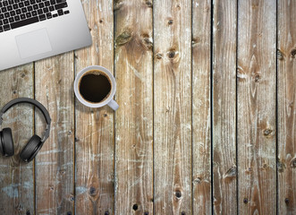 Office business desk mock up with laptop, headphones and coffee. Wooden background