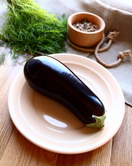 beautiful dark aubergine beige ceramic plate on a wooden table canvas cloth beam dill wooden bowl with herbs top view