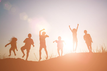 Silhouette Children playing on summer sunset happy time