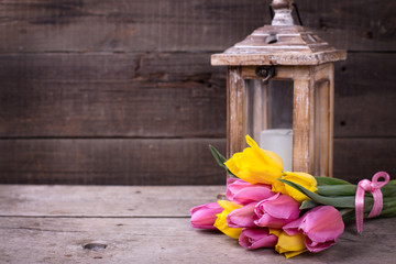 Bunch  yellow and pink spring tulips  and candle in lantern on v