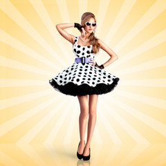 Dotted dress / Creative photo of a vogue pin-up girl, dressed in a retro polka-dot dress and sunglasses, posing on colorful abstract cartoon style background.