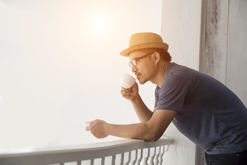 Young hipster man resting at home balcony with the sunrise