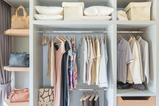 clothes hanging on rail in wooden closet