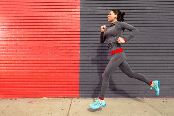 Female runner jogging sprinting in urban setting red gray exercise in motion
