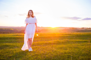 Girl Outdoors enjoying nature. Woman in white dress on Field