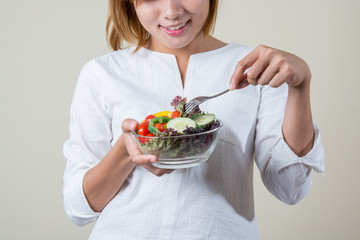 beautiful woman standing holding bowl of salad eating some veget