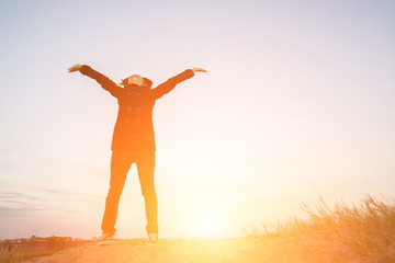 Young woman open arms under the sunrise at mountain