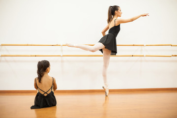 Girl watching a real dancer do barre work