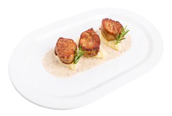Fried pork tenderloin medallions on mashed potatoes.