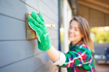 Cheerful woman applying protective varnish or paint on wooden house tongue and groove cladding elevation wall. Focus on hand with brush. House improvement diy concept.