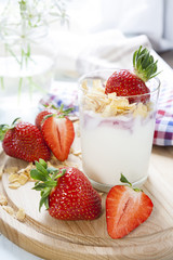 Homemade healthy dessert in a glass with yogurt, fresh strawberry and corn flakes for breakfast with fresh white flowers and checkered napkin on wooden table, closeup