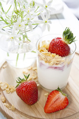 Homemade healthy dessert in a glass with yogurt, fresh strawberry and corn flakes for breakfast with fresh white flowers on wooden table, closeup