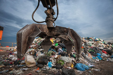 Close up of mechanical arm grabbing waste from a pile at city landfill