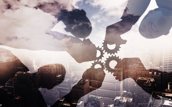 Composite image of business colleagues holding cog