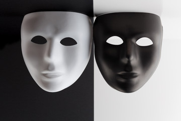 Black and white masks on contrasting backgrounds hanging from the ceiling.