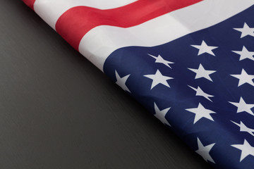 Folded fragment of American flag on black chalkboard. Horizontal image with copy space.