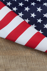 Fragment of USA flag folded on wooden walnut table. Vertical image with copy space.