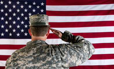 Veteran male solider saluting the flag of USA