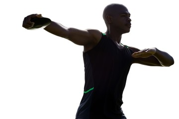 Dark picture of sportsman is practising discus throw