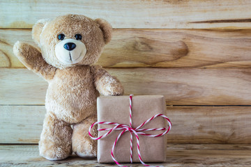 Teddy bear standing beside brown gift box