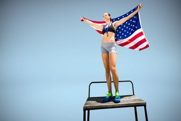 Composite image of an athletic woman wearing american flag and m