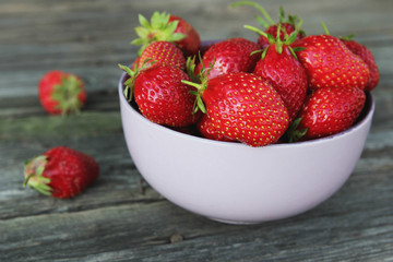 Appetizing fresh juicy strawberries in the bowl on the wooden background