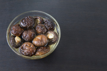 Dried Chinese mushroom in water on black wooden background.