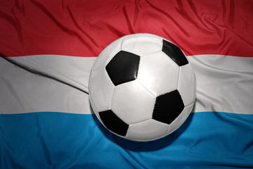 black and white football ball on the national flag of luxembourg
