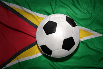 black and white football ball on the national flag of guyana