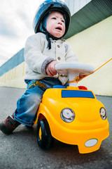 little boy crying while sitting on car