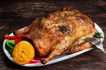 Roast Duck and oranges on a black wooden table.