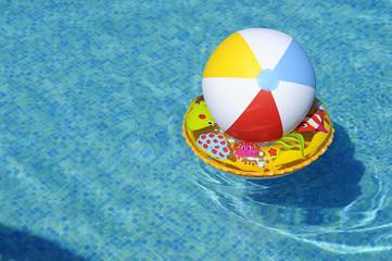 Obraz Dmuchane zabawki dryfujące po wodzie w basenie - piłka i koło - fototapety do salonu