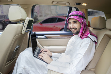 Arabic man working in car and smiling