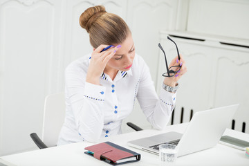 Businesswoman at the desk, feeling tired and has a headache