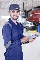 Asian mechanic with clipboard in workshop