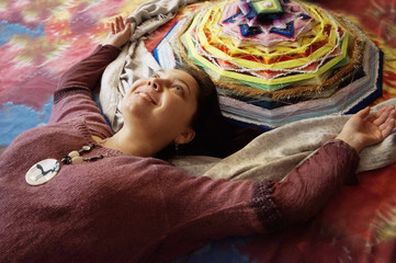 girl with multi-colored  mandala in American Native style, hand woven from threads based on wooden rods, is lying on a colorful background