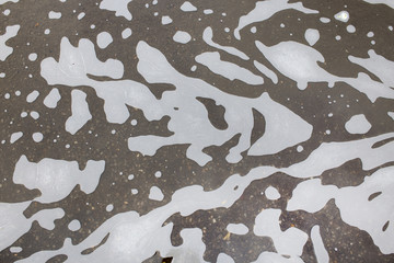 puddle with foam and dirty water. background of dirty water with spots like a camouflage pattern