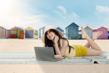 Woman using a laptop at the beach