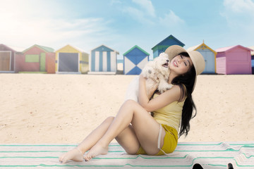 Woman with maltese dog on the beach