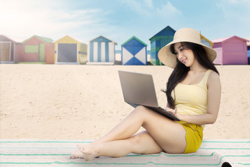 Woman working with laptop on the beach