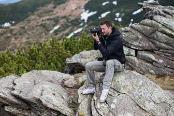 Nature photographer with digital camera on top of the mountain.