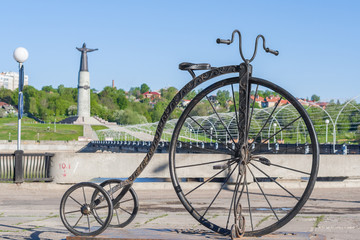 Monument to the bike with a large front wheel on the bay in Cheboksary, Chuvash Republic. Russia. In the background manument patroness mother. 05/14/2016