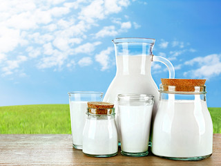 Pitcher, jars and glasses of milk on wooden table against green field and blue sky background
