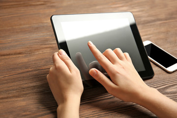 Mobile phone and female hands using tablet, on the wooden background