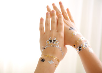 Silver and golden flash tattoo on female hands over white background