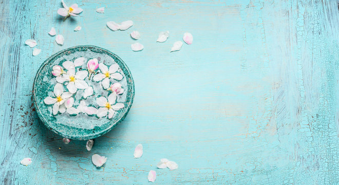 Beautiful spring blossom with white flowers in water bowl on Turquoise blue shabby chic wooden background, top view. Wellness and spa concept. Spring blossom background, banner