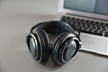 Headphones and laptop on table closeup