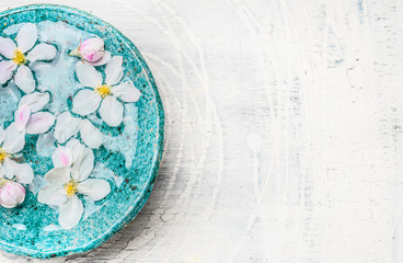 White flowers in turquoise blue water bowl on light shabby chic wooden background, top view, place for text. Wellness and spa concept. Spring blossom background