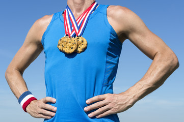 Athlete wearing chocolate chip cookies gold medals standing in front of blue sky background
