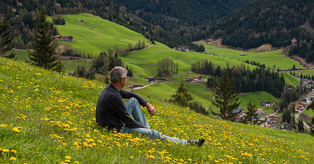 Man is relaxing in a field at Funes valley
